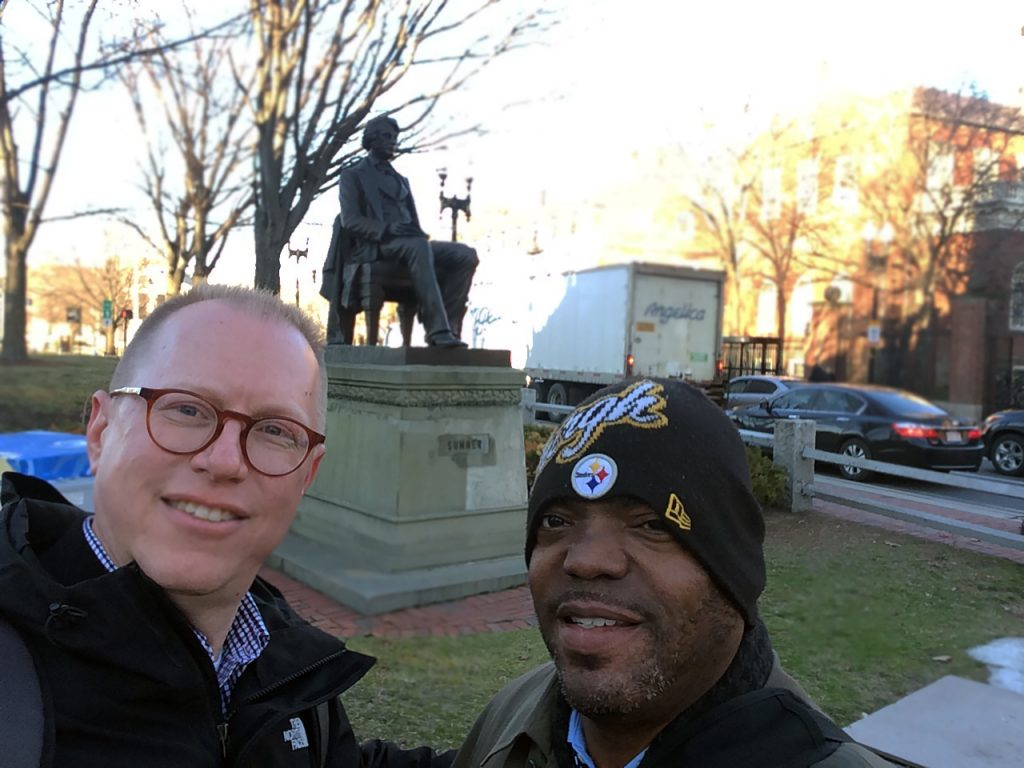 "Jeff Jackson (left) and Chuck Ross (right) posing with the statue of abolitionist Senator Charles Sumner while in Cambridge, Massachusetts, for the ""Universities and Slavery: Bound by History"" conference at the Radcliffe Institute for Advanced Study at Harvard University. Photo by Jeffrey Jackson, March 2017."